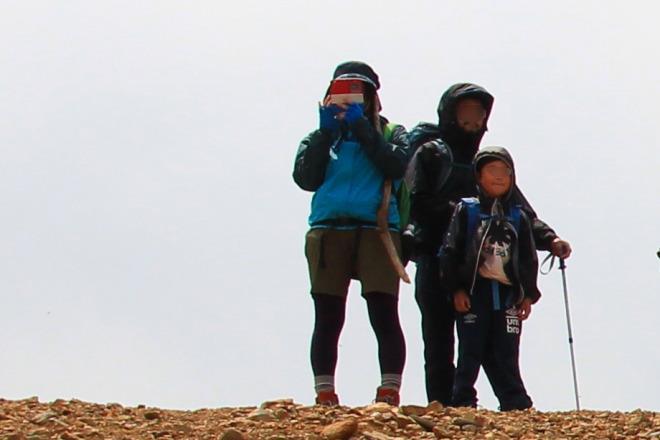 防寒対策した山頂の登山者たち